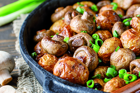 Delicious baked potatoes in cast-iron pan with champignons and g