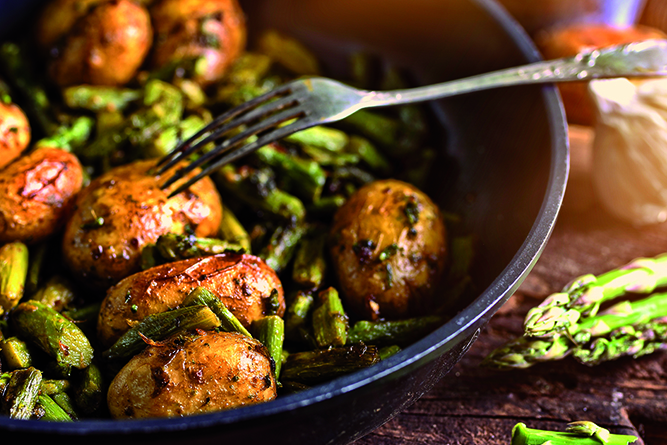 asparagus with potatoes fried in a pan with herbs